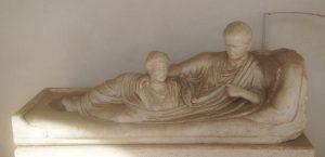 Fig 2 : Kline: monument funéraire sur lequel le défunt est allongé, en toge, et tient dans ses bras le buste d'une femme morte. Mabre, fin du Ier s. ap. J.-C. Rome, Terme di Diocleziano (c) A. Arghyris